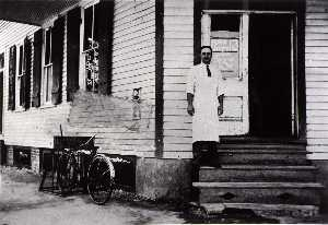 Betty Tichich - Henry Macrini in doorway of store, H M Grocery at 1627 Avenue H, 1928, from The Corner Stores of Galveston, Galveston County Cultural Arts Council